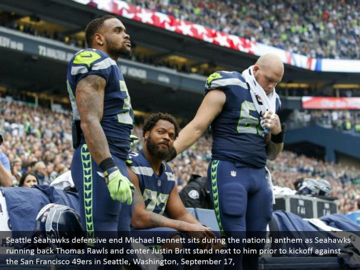 Seattle Seahawks defensive end Michael Bennett sits during the national anthem as Seahawks running back Thomas Rawls and center Justin Britt stand next to him prior to kickoff against the San Francisco 49ers in Seattle, Washington, September 17,