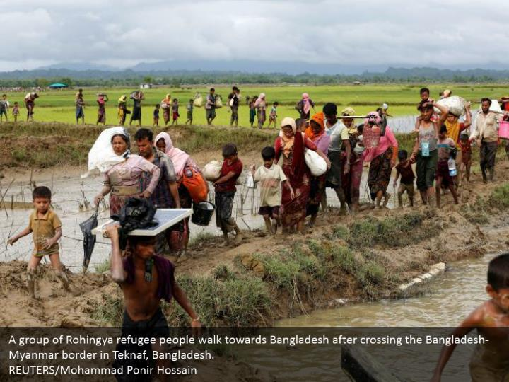 A group of Rohingya refugee people walk towards Bangladesh after crossing the Bangladesh-Myanmar border in Teknaf, Bangladesh.  REUTERS/Mohammad Ponir Hossain
