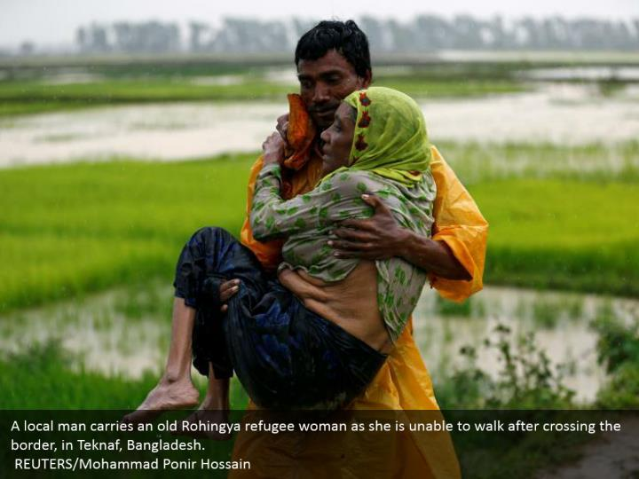 A local man carries an old Rohingya refugee woman as she is unable to walk after crossing the border, in Teknaf, Bangladesh.  REUTERS/Mohammad Ponir Hossain