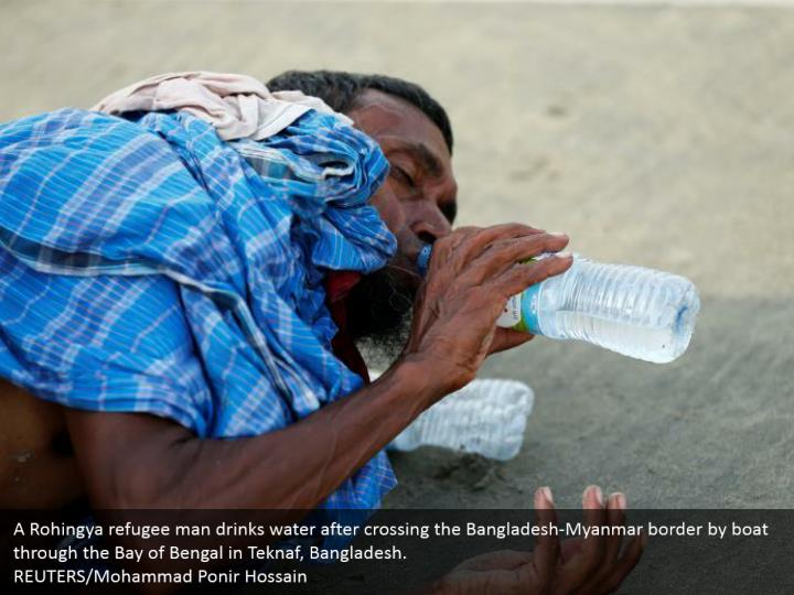 A Rohingya refugee man drinks water after crossing the Bangladesh-Myanmar border by boat through the Bay of Bengal in Teknaf, Bangladesh.  REUTERS/Mohammad Ponir Hossain