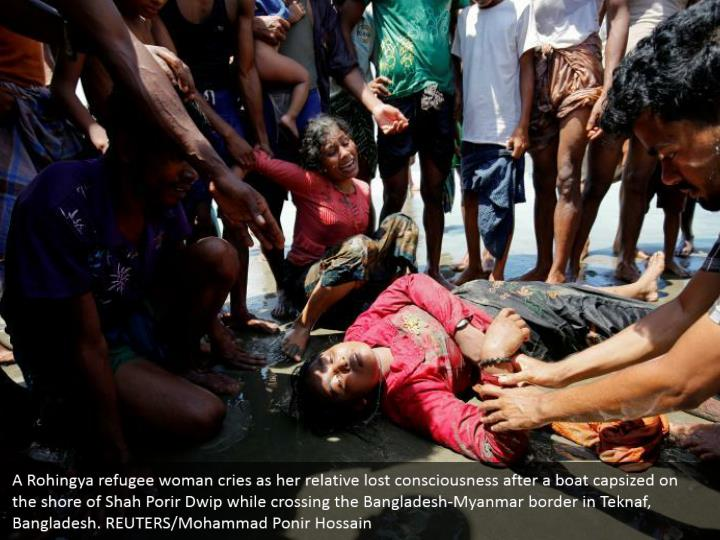 A Rohingya refugee woman cries as her relative lost consciousness after a boat capsized on the shore of Shah Porir Dwip while crossing the Bangladesh-Myanmar border in Teknaf, Bangladesh. REUTERS/Mohammad Ponir Hossain