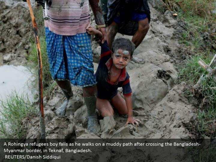 A Rohingya refugees boy falls as he walks on a muddy path after crossing the Bangladesh-Myanmar border, in Teknaf, Bangladesh.  REUTERS/Danish Siddiqui
