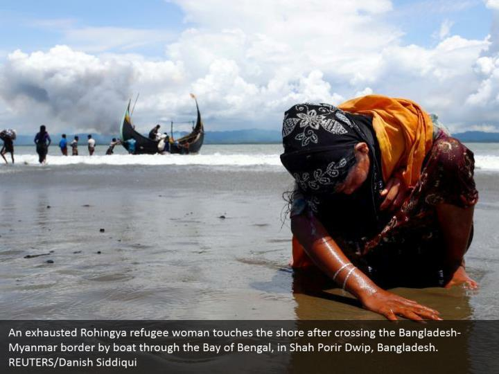 An exhausted Rohingya refugee woman touches the shore after crossing the Bangladesh-Myanmar border by boat through the Bay of Bengal, in Shah Porir Dwip, Bangladesh.  REUTERS/Danish Siddiqui