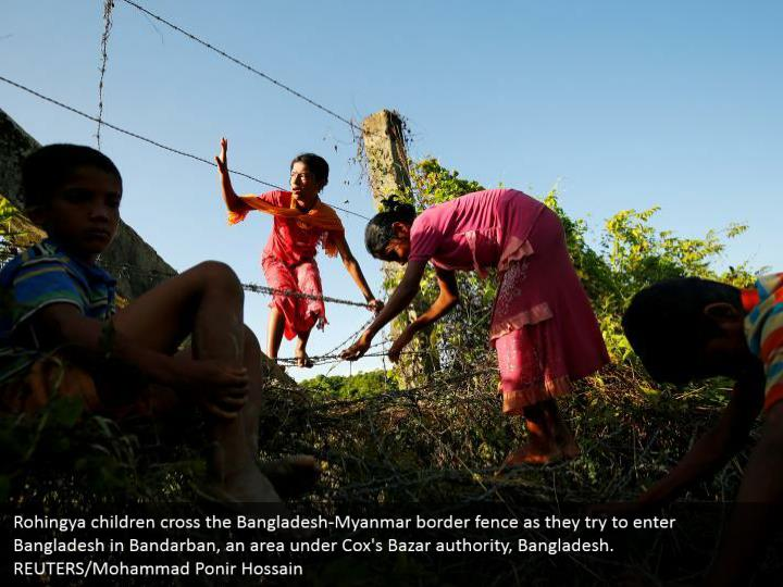 Rohingya children cross the Bangladesh-Myanmar border fence as they try to enter Bangladesh in Bandarban, an area under Cox's Bazar authority, Bangladesh.  REUTERS/Mohammad Ponir Hossain