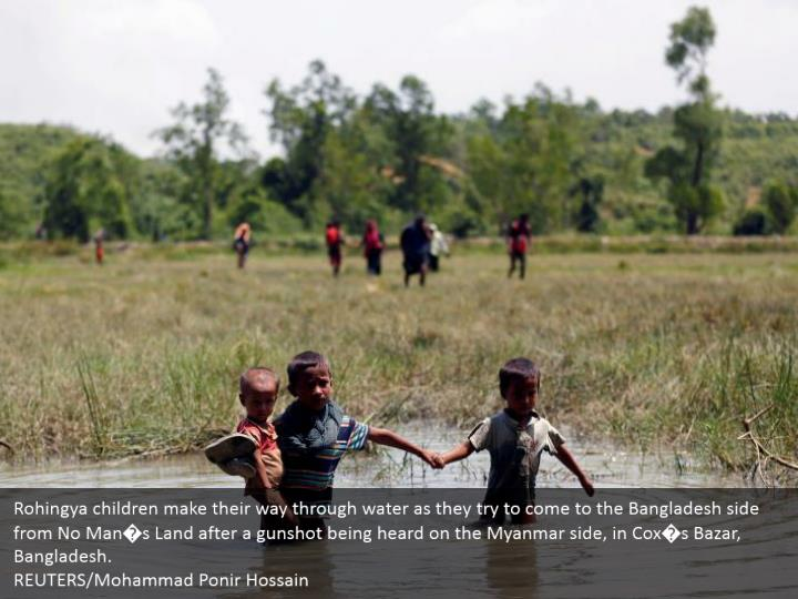 Rohingya children make their way through water as they try to come to the Bangladesh side from No Man�s Land after a gunshot being heard on the Myanmar side, in Cox�s Bazar, Bangladesh.  REUTERS/Mohammad Ponir Hossain
