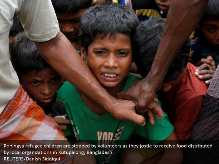 Rohingya refugee children are stopped by volunteers as they jostle to receive food distributed by local organizations in Kutupalong, Bangladesh.  REUTERS/Danish Siddiqui