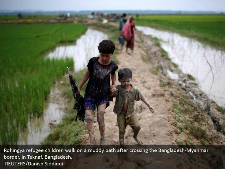 Rohingya refugee children walk on a muddy path after crossing the Bangladesh-Myanmar border, in Teknaf, Bangladesh.  REUTERS/Danish Siddiqui