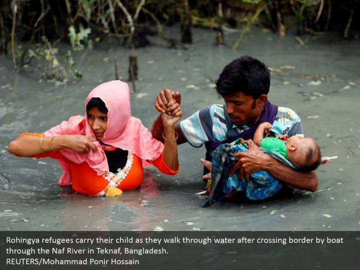 Rohingya refugees carry their child as they walk through water after crossing border by boat through the Naf River in Teknaf, Bangladesh.  REUTERS/Mohammad Ponir Hossain