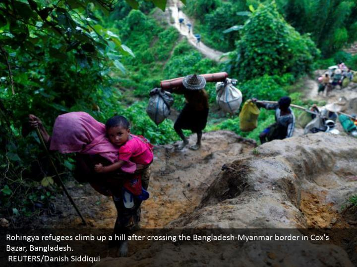 Rohingya refugees climb up a hill after crossing the Bangladesh-Myanmar border in Cox's Bazar, Bangladesh.  REUTERS/Danish Siddiqui