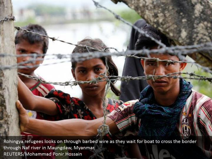 Rohingya refugees looks on through barbed wire as they wait for boat to cross the border through Naf river in Maungdaw, Myanmar. REUTERS/Mohammad Ponir Hossain