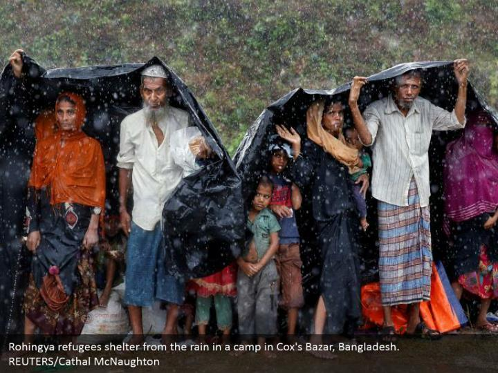 Rohingya refugees shelter from the rain in a camp in Cox's Bazar, Bangladesh.  REUTERS/Cathal McNaughton