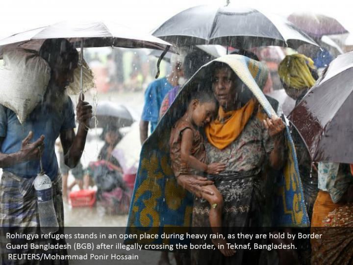 Rohingya refugees stands in an open place during heavy rain, as they are hold by Border Guard Bangladesh (BGB) after illegally crossing the border, in Teknaf, Bangladesh.  REUTERS/Mohammad Ponir Hossain
