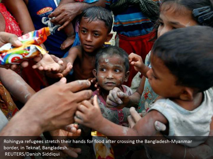 Rohingya refugees stretch their hands for food after crossing the Bangladesh-Myanmar border, in Teknaf, Bangladesh.  REUTERS/Danish Siddiqui