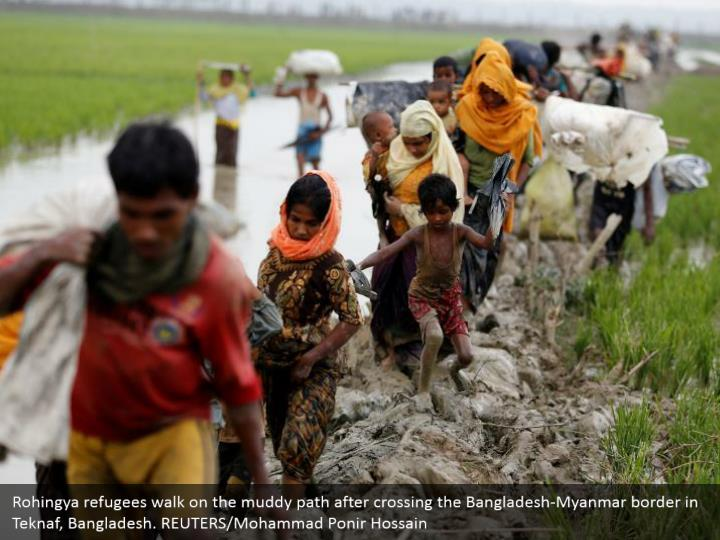 Rohingya refugees walk on the muddy path after crossing the Bangladesh-Myanmar border in Teknaf, Bangladesh. REUTERS/Mohammad Ponir Hossain