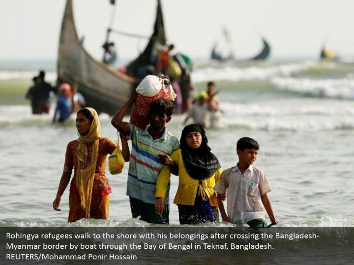 Rohingya refugees walk to the shore with his belongings after crossing the Bangladesh-Myanmar border by boat through the Bay of Bengal in Teknaf, Bangladesh.  REUTERS/Mohammad Ponir Hossain