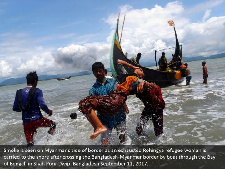 Smoke is seen on Myanmar's side of border as an exhausted Rohingya refugee woman is carried to the shore after crossing the Bangladesh-Myanmar border by boat through the Bay of Bengal, in Shah Porir Dwip, Bangladesh September 11, 2017.
