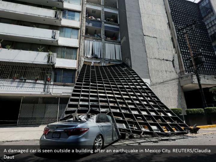 A damaged car is seen outside a building after an earthquake in Mexico City. REUTERS/Claudia Daut