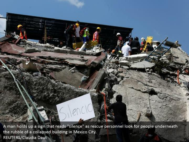 "A man holds up a sign that reads ""silence"" as rescue personnel look for people underneath the rubble of a collapsed building in Mexico City.  REUTERS/Claudia Daut"