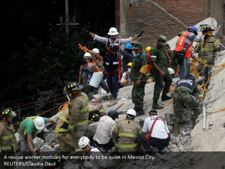A rescue worker motions for everybody to be quiet in Mexico City.  REUTERS/Claudia Daut