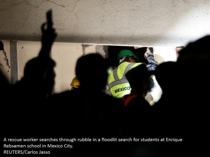 A rescue worker searches through rubble in a floodlit search for students at Enrique Rebsamen school in Mexico City.  REUTERS/Carlos Jasso