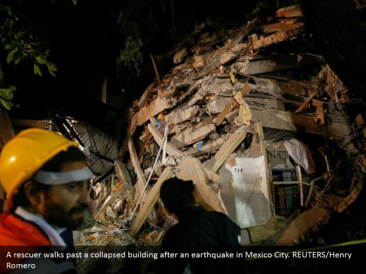 A rescuer walks past a collapsed building after an earthquake in Mexico City. REUTERS/Henry Romero