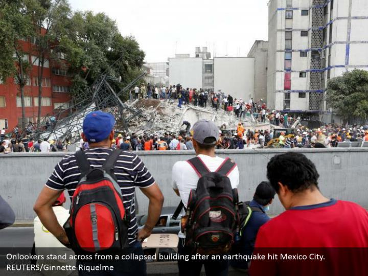 Onlookers stand across from a collapsed building after an earthquake hit Mexico City. REUTERS/Ginnette Riquelme