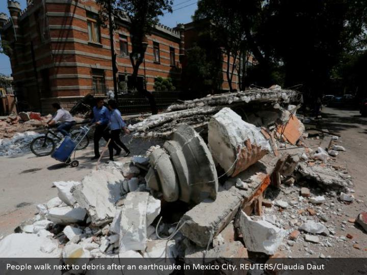 People walk next to debris after an earthquake in Mexico City. REUTERS/Claudia Daut
