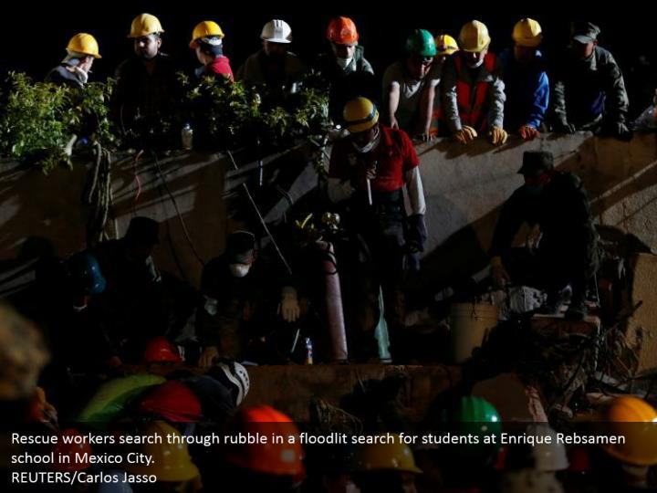 Rescue workers search through rubble in a floodlit search for students at Enrique Rebsamen school in Mexico City.  REUTERS/Carlos Jasso
