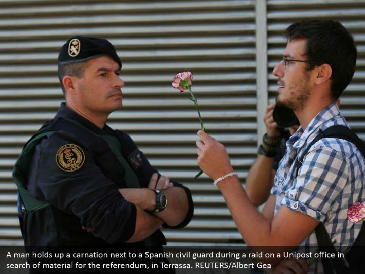 A man holds up a carnation next to a Spanish civil guard during a raid on a Unipost office in search of material for the referendum, in Terrassa. REUTERS/Albert Gea