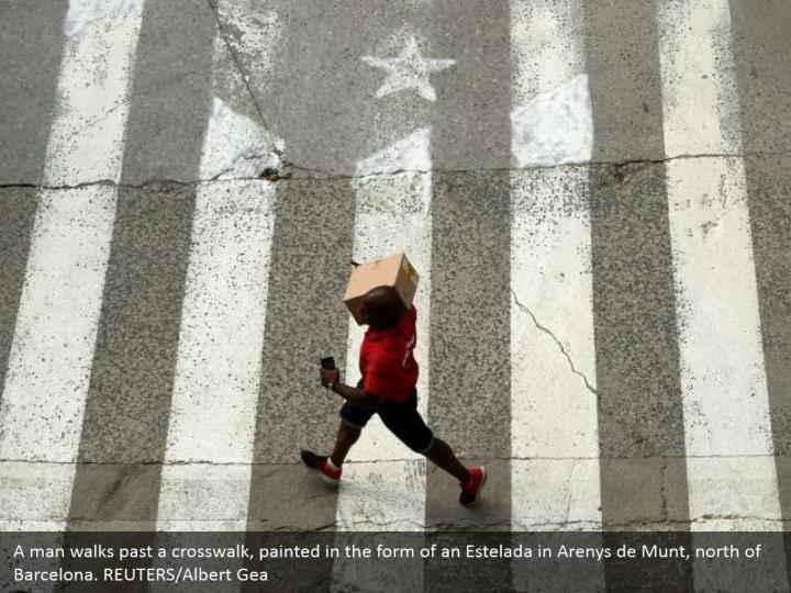 A man walks past a crosswalk, painted in the form of an Estelada in Arenys de Munt, north of Barcelona. REUTERS/Albert Gea