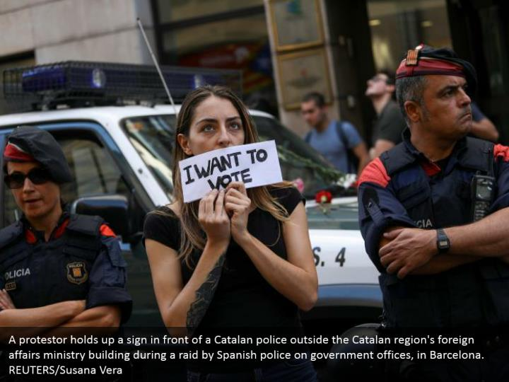 A protestor holds up a sign in front of a Catalan police outside the Catalan region's foreign affairs ministry building during a raid by Spanish police on government offices, in Barcelona. REUTERS/Susana Vera