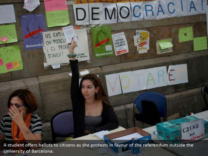 A student offers ballots to citizens as she protests in favour of the referendum outside the University of Barcelona.