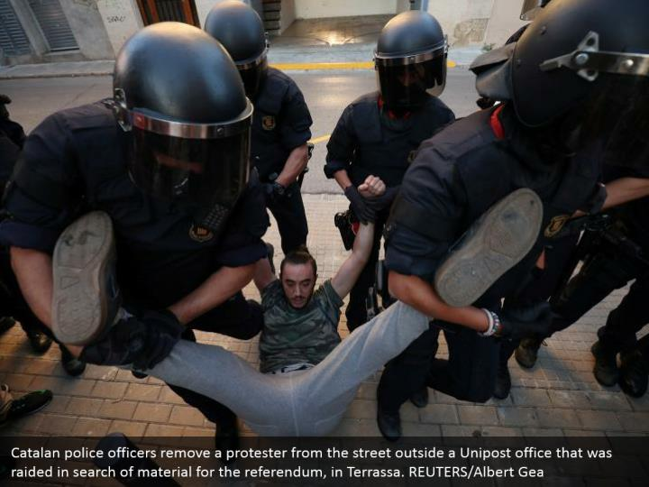 Catalan police officers remove a protester from the street outside a Unipost office that was raided in search of material for the referendum, in Terrassa. REUTERS/Albert Gea