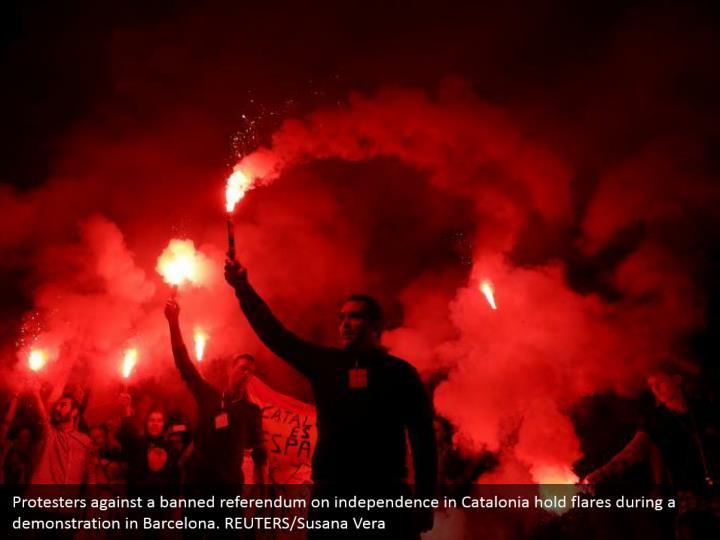 Protesters against a banned referendum on independence in Catalonia hold flares during a demonstration in Barcelona. REUTERS/Susana Vera