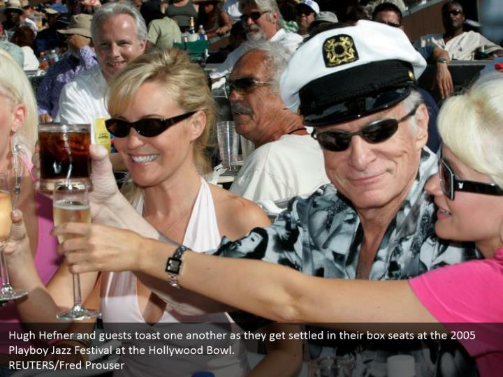 Hugh Hefner and guests toast one another as they get settled in their box seats at the 2005 Playboy Jazz Festival at the Hollywood Bowl.  REUTERS/Fred Prouser