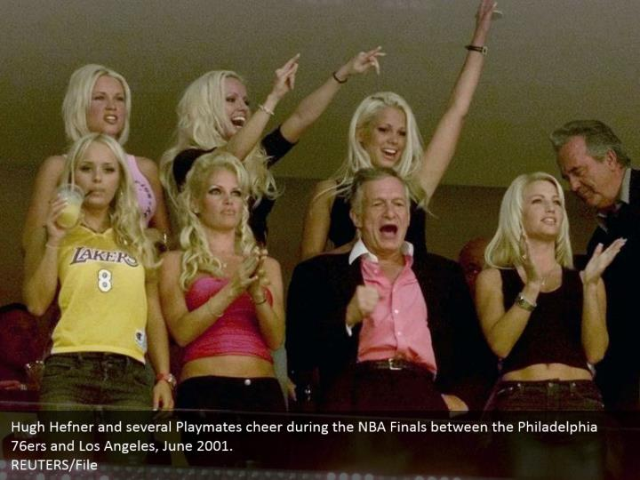 Hugh Hefner and several Playmates cheer during the NBA Finals between the Philadelphia 76ers and Los Angeles, June 2001. REUTERS/File