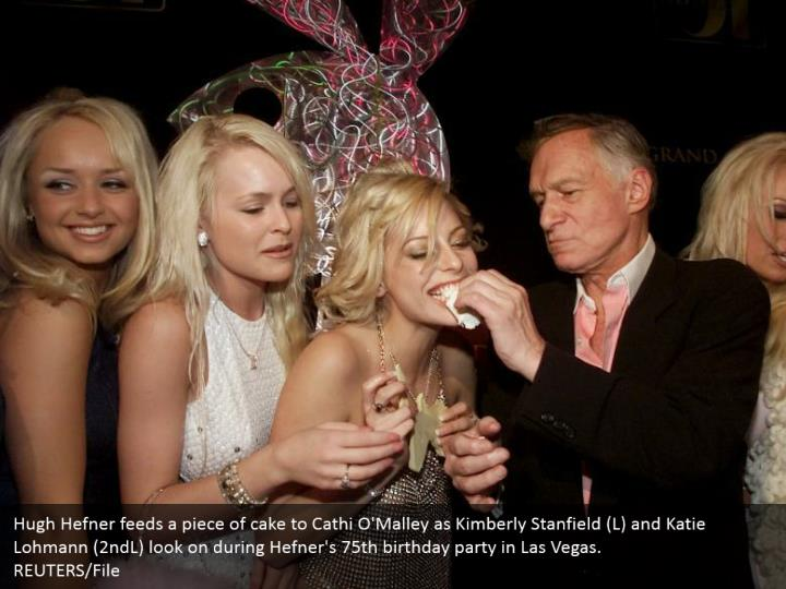 Hugh Hefner feeds a piece of cake to Cathi O'Malley as Kimberly Stanfield (L) and Katie Lohmann (2ndL) look on during Hefner's 75th birthday party in Las Vegas. REUTERS/File