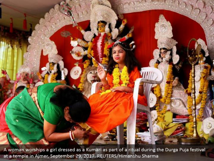 A woman worships a girl dressed as a Kumari as part of a ritual during the Durga Puja festival at a temple in Ajmer, September 29, 2017. REUTERS/Himanshu Sharma