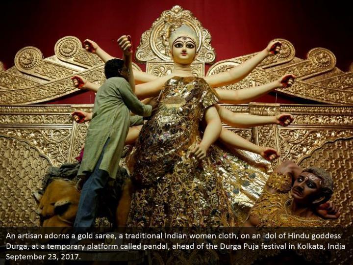 An artisan adorns a gold saree, a traditional Indian women cloth, on an idol of Hindu goddess Durga, at a temporary platform called pandal, ahead of the Durga Puja festival in Kolkata, India September 23, 2017.