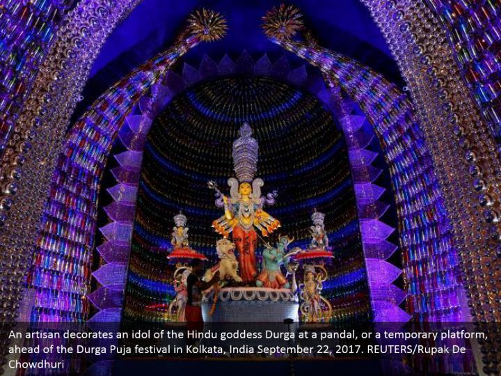 An artisan decorates an idol of the Hindu goddess Durga at a pandal, or a temporary platform, ahead of the Durga Puja festival in Kolkata, India September 22, 2017. REUTERS/Rupak De Chowdhuri