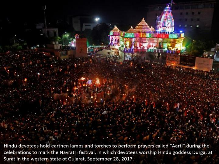 "Hindu devotees hold earthen lamps and torches to perform prayers called ""Aarti"" during the celebrations to mark the Navratri festival, in which devotees worship Hindu goddess Durga, at Surat in the western state of Gujarat, September 28, 2017."