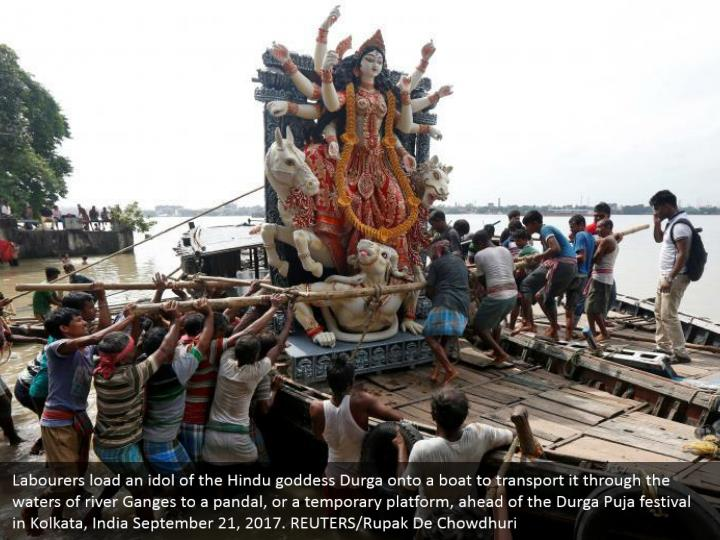 Labourers load an idol of the Hindu goddess Durga onto a boat to transport it through the waters of river Ganges to a pandal, or a temporary platform, ahead of the Durga Puja festival in Kolkata, India September 21, 2017. REUTERS/Rupak De Chowdhuri