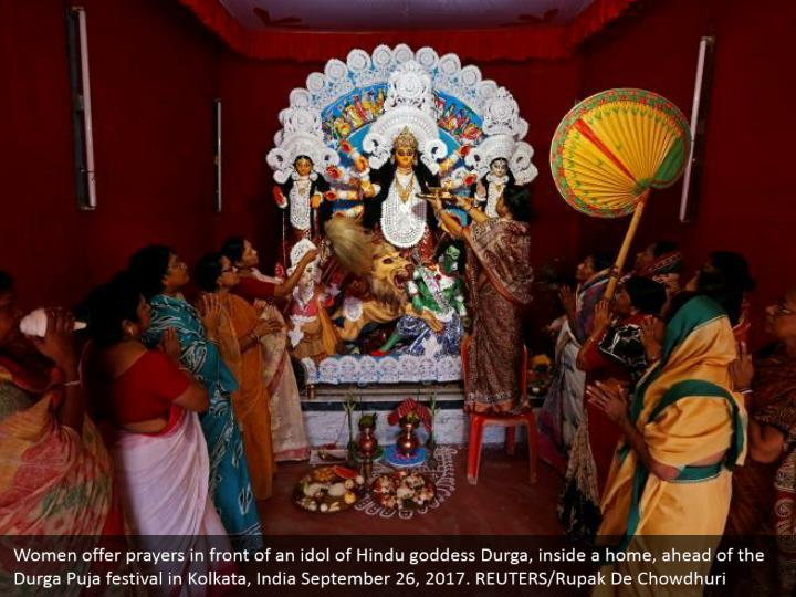 Women offer prayers in front of an idol of Hindu goddess Durga, inside a home, ahead of the Durga Puja festival in Kolkata, India September 26, 2017. REUTERS/Rupak De Chowdhuri