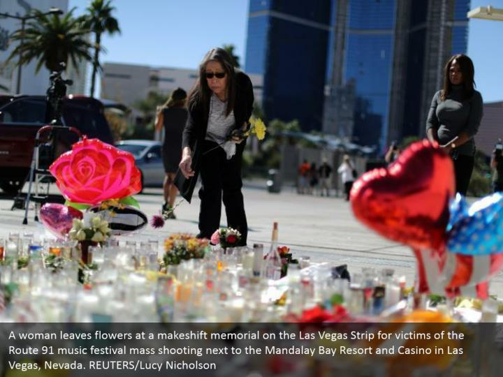 A woman leaves flowers at a makeshift memorial on the Las Vegas Strip for victims of the Route 91 music festival mass shooting next to the Mandalay Bay Resort and Casino in Las Vegas, Nevada. REUTERS/Lucy Nicholson