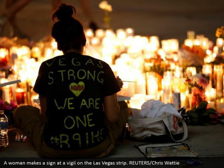 A woman makes a sign at a vigil on the Las Vegas strip. REUTERS/Chris Wattie