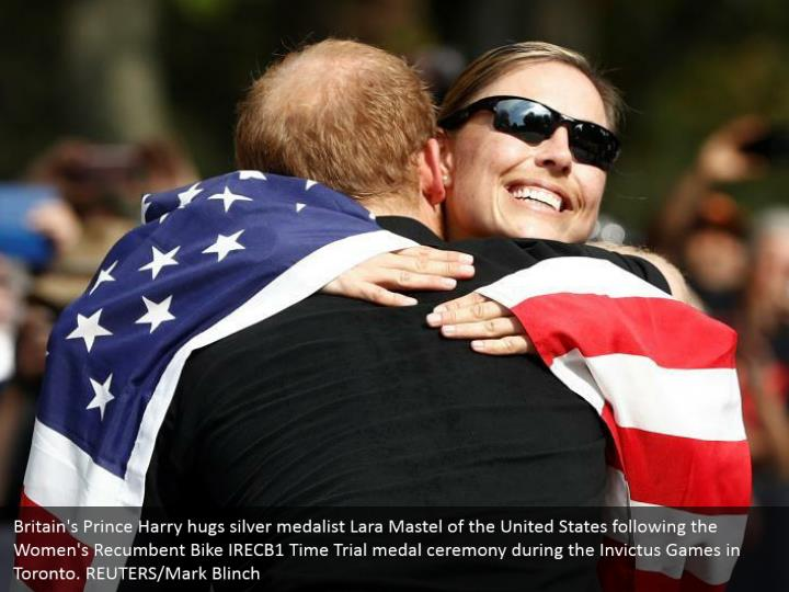 Britain's Prince Harry hugs silver medalist Lara Mastel of the United States following the Women's Recumbent Bike IRECB1 Time Trial medal ceremony during the Invictus Games in Toronto. REUTERS/Mark Blinch