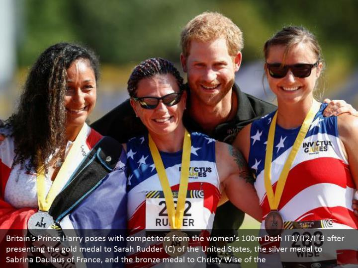 Britain's Prince Harry poses with competitors from the women's 100m Dash IT1/IT2/IT3 after presenting the gold medal to Sarah Rudder (C) of the United States, the silver medal to Sabrina Daulaus of France, and the bronze medal to Christy Wise of the