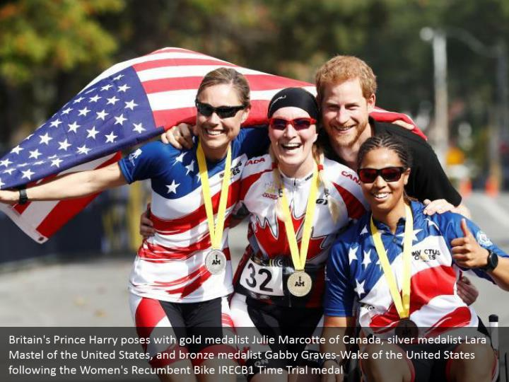 Britain's Prince Harry poses with gold medalist Julie Marcotte of Canada, silver medalist Lara Mastel of the United States, and bronze medalist Gabby Graves-Wake of the United States following the Women's Recumbent Bike IRECB1 Time Trial medal