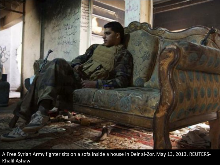 a free syrian army fighter sits on a sofa inside n.