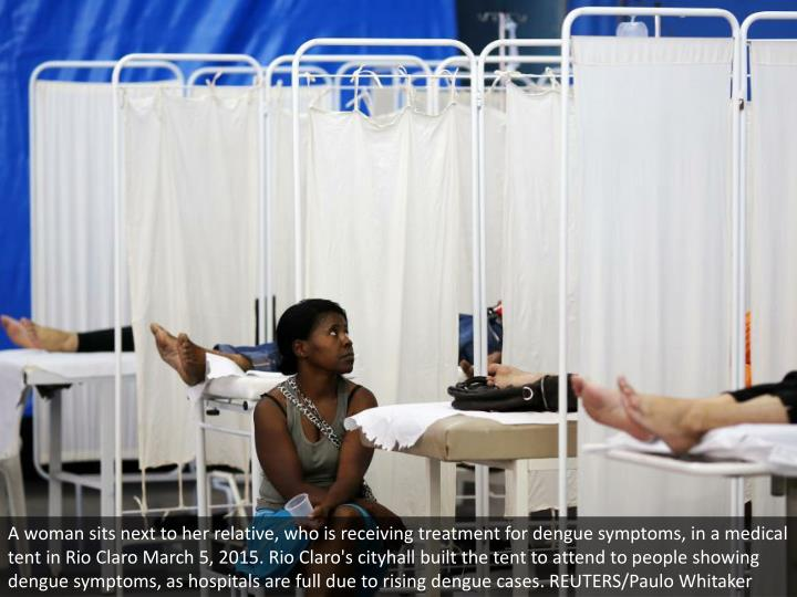 A woman sits next to her relative, who is receiving treatment for dengue symptoms, in a medical tent...